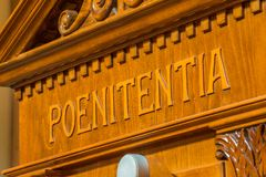 Latin word on a wooden confessional. The Latin word poenitentia meaning repentance Stock Images