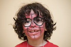 Latin Young Boy Painted Face. Painting masked Latin boy enjoying the final moments of a birthday party Stock Images