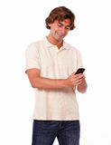 Latin young man in jeans reading on cellphone Stock Photo