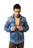 Latin young man opening denim shirt on naked chest. Muscular build Royalty Free Stock Photography