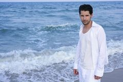 Latin young man white shirt walking blue beach Royalty Free Stock Images