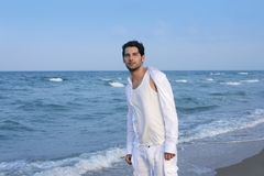 Latin young man white shirt walking blue beach Stock Photo