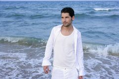 Latin young man white shirt walking blue beach Stock Photography