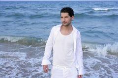 Latin young man white shirt walking blue beach Stock Photography