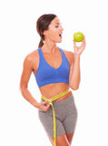 Latin young woman biting apple to lose weight. Latin young woman in sport clothing biting an apple to lose weight on isolated background Stock Images