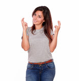 Latin young woman crossing her fingers for luck. Portrait of a latin young woman crossing her fingers for luck on isolated background Royalty Free Stock Photos