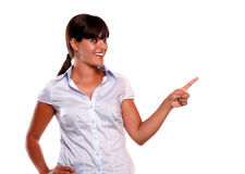 Latin young woman looking and pointing her left. On isolated background - copyspace Royalty Free Stock Photo