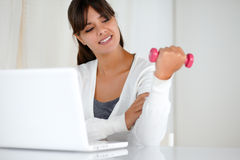 Latin young woman with weights in front of laptop Stock Photos