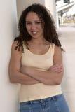 Latina assez jeune avec le cheveu bouclé dans le réservoir jaune images libres de droits