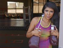 Latina Beauty Boxing. Beautiful brunette Latina model holding boxing gloves in doorway at traditional boxing gym Royalty Free Stock Images