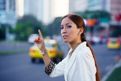 Latina businesswoman calling taxi car leaving work Royalty Free Stock Images
