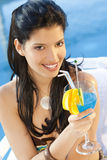 Latina Cocktail. A stunningly beautiful young hispanic woman looking drinking a cocktail next to a swimming pool royalty free stock image