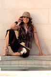 Latina Fedora. Glamorous young Latina in a fedora sitting in an alabaster courtyard royalty free stock photos