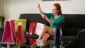 Latina flicka med halsbandet för försök för shoppingpåsar på soffan Arkivfoton