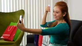 Latina flicka med shoppingpåsar som tar Selfie med telefonen Royaltyfri Fotografi