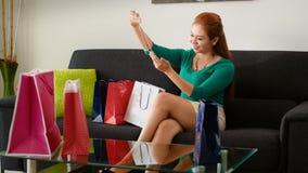 Latina flicka, når att ha shoppat blickmodehalsbandet på soffan Royaltyfri Fotografi