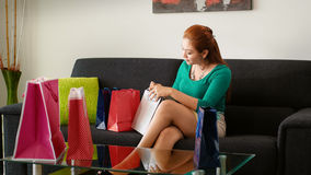 Latina Girl Peeps Into Shopping Bags On Sofa At Home Royalty Free Stock Photo