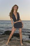 Latina hermosa que se coloca en rocas en la playa imagenes de archivo