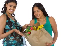 Latina and Indian shopping Fresh vegetables. Two young ethnic women indian and hispanic with paper groceries bag of fresh vegetables Stock Photos