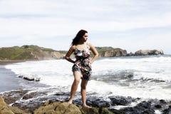 Latina kobiety pozycja Na skałach Przy plażą W sukni Zdjęcia Royalty Free