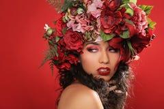 Latina kvinna med den blom- huvudbonaden på rött Arkivbilder