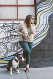 Latina Millennial ställningar mot väggen med hennes husdjurhund Bull terrier som sitter vid hennes sida arkivbild