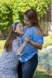 Latina moder och dotter som ler och skrattar yttersidan i bakg?rd royaltyfri fotografi