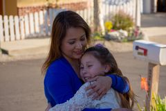 Latina Mother and Daughter smiling and laughing outside under a tree stock photography