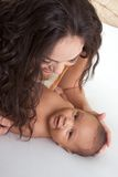 Latina mother playing with her baby boy son on bed Stock Photography