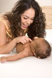 Latina mother playing with her baby boy son on bed Royalty Free Stock Photography