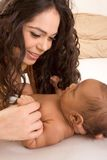 Latina mother playing with her baby boy son on bed Stock Image