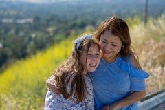 Latina-Mutter und -tochter, die auf einem H?gel vor gelben Blumen l?cheln und lachen lizenzfreie stockfotografie