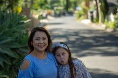 Latina-Mutter und -tochter, die auf Vorstadtstra?e l?cheln und lachen stockbild