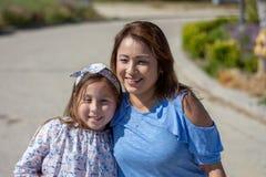 Latina-Mutter und -tochter, die auf Vorstadtstra?e l?cheln und lachen stockbilder
