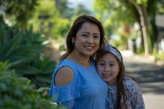 Latina-Mutter und -tochter, die auf Vorstadtstra?e l?cheln und lachen stockfotografie
