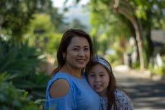 Latina-Mutter und -tochter, die auf Vorstadtstra?e l?cheln und lachen lizenzfreie stockbilder