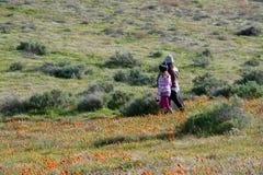 Latina-Mutter und Tochter vor Wüste Kalifornien-Mohnblumenfeld auf Weg mit den orange und gelben Blumen lizenzfreie stockfotografie