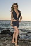 Latina-Schönheit, die auf Felsen am Strand steht Lizenzfreies Stockbild