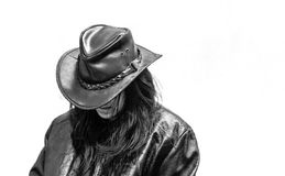 Latina teen in black hat and leather jacket. Latina teenager with face concealed wearing a black hat and black leather jacket looking downwards Royalty Free Stock Photography