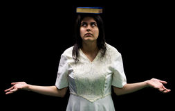 Latina teen with book on head. Latina teenager in white dress standing in front of black background balancing book on her head and rolling her eyes Stock Images