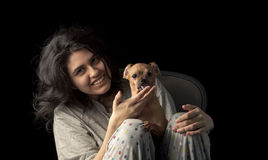 Latina teen with dog. Low key shot of latina teenage girl holding her chihuahua dog and looking at the camera with a smile on her face; the dog's ears are curled Royalty Free Stock Photo