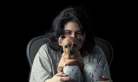 Latina teen with dog. Low key shot of latina teenage girl looking at her chihuahua, with her face partially hidden by the dog's head; the dog's ears are curled Stock Photos