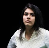 Latina teen in white on black backdrop. Latina teenager in white standing in front of a black background with an angry, suspicious, serious look on her face Royalty Free Stock Photos