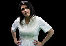 Latina teen in white on black background. Latina teenager in white standing in front of a black background with hands on hips and a serious look on her face Stock Image
