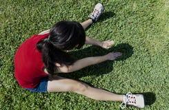 Hispanic Teen Woman Sitting On Green Grass Stretching. Latina Teen Woman Red Top Blue Shorts Stretching On Green Grass Outdoors stock image
