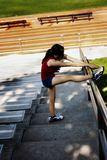 Hispanic Teen Woman Stretching With Leg Up On Rail. Latina Teen Woman Streching Leg Up On Rail Of Stairs At Track Red Top Blue Shorts royalty free stock photos