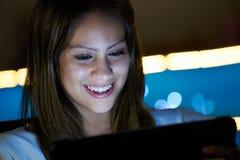 Latina tonåring som använder socialt massmedia på minnestavlaPC på natten Royaltyfri Bild