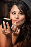 Latina Woman with Compact Applying Lip Gloss Stock Photography