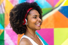 Latina woman listing to music on colorful background Stock Photo