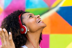 Latina woman listing to music on colorful background Stock Image